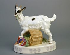 Meissen goat standing astride and over turned basket of flowers.