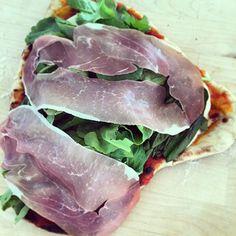 Hot off our grill - pizza margarita + wild arugula and prosciutto. #summer #grilling
