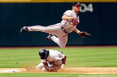 Former Atlanta Braves second baseman Marcus Giles leaps over an opposing player to complete a double play