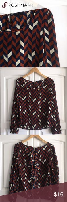 Patterned top with ruffle back! The colors are navy, light brown, and cream. Juniors large but fits a ladies medium. This top stands alone and makes a statement. Pretty ruffle down the back. Brand: Edge Tops Blouses
