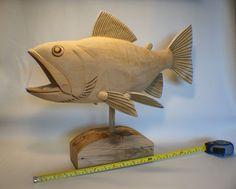 A big, unpainted, wooden trout sculpture.