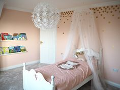 peach and gold girl's bedroom with gold spot stickers and bed canopy