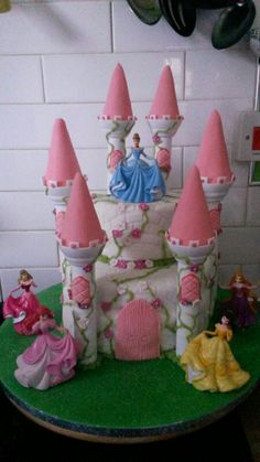 Princess castle cake. Two tier cake i made for daughters 4th bday. Bottom is normal sponge top is lemon. I used Wilton turrets and iced them along with disney princess figures. Brick impression matt for fondant icing.