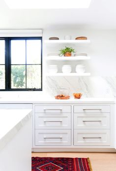 White walls, white countertops, white cabinets, black framed windows, white shelves, and white dishes