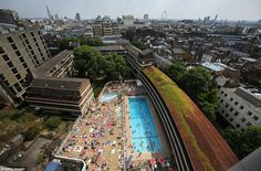 London sunshine: Swimmers enjoy an outdoor pool in central London today, with the city's famous landmarks visible in the distance