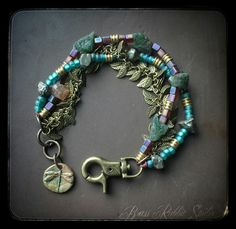 Beaded bracelet in rich greens, golds, and lavender. Artisan bronze dragonfly charm by Cristina Leonard, rough apatite nuggets, miuki cube beads, raw brass spacers, czeck glass, free form faceted pyrite nuggets, mystic quartz nugget, brass fringe chain, brass lobster clasp and a short chain tail that gives it an adjustable fit.