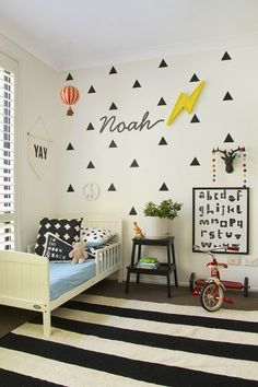 Graphic black and white little boy's room. Triangle cut outs on one wall, painted stepstool. framed alphabet placement!), graphic patterned pillows, banner, bits of red (knobs) toys, peace sign painted white, antler head hook, name or first name letter in script using black contact type paper IKEA rug?, trike?