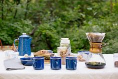 Table in a garden, with a coffee maker, mugs and bowls, a cake and cereal. Bowls, Cereal, Coffee Maker, Bakery, Mugs, Garden, Table, Serving Bowls, Coffee Maker Machine
