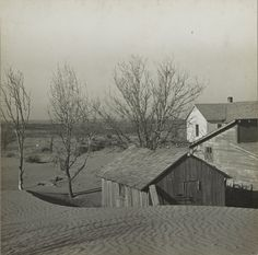 Scene from a Kansas farm during the Dust Bowl.  Drifts of sand pile up beside the barns and farmhouse against the barren backdrop of drought-ravaged Kansas in this 1936 photograph