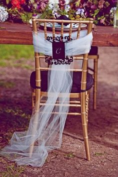 Monogram on the back of the bride & groom's chair with a tulle bow.  (would be cute with signs that said mr. and mrs. too!)