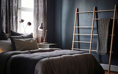 A dark-walled bedroom with a window, a bed, a bedside table, and a blanket ladder.