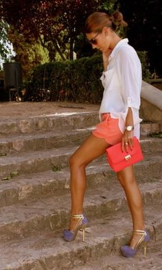 I love this outfit; white blouse with the coral shorts/clutch......striking!