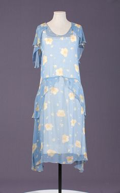 The 1920s day dress is blue chiffon with creamy, yellow flowers.  A pretty summer frock for a garden party.  From Seneca Fashion Resource Centre.