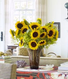 In Brian McCarthy and Daniel Sager's Kerhonkson, New York, house, a bright bouquet of sunflowers sits on a suzani-covered table.   - HouseBeautiful.com