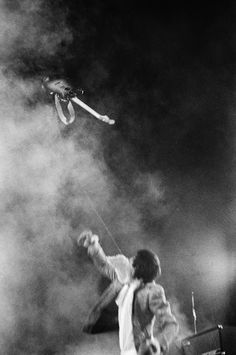 Pete Townshend tosses his guitar in mid-air, on stage at Atwood Stadium in Flint, MI