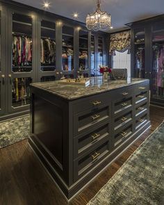 Glam black closet features a black closet island adorned with brass pulls topped with black marble ...