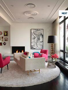 Jonathon Adler Cool modern interior with hot pink pops, round shag white rug, black floor
