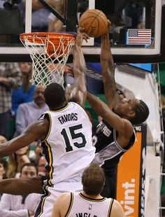 Utah Jazz forward Derrick Favors (15) blocking a shot by San Antonio Spurs forward Kawhi Leonard (2) , but was called for the foul as the Utah Jazz defeat the San Antonio Spurs 100-96 in NBA basketball Tuesday, Dec. 9, 2014, in Salt Lake City. (Tom Smart, Deseret News)
