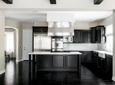 Black kitchen cabinets and sleek quartz countertops offer a polished look.