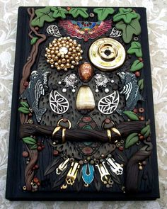 A 'found object' journal cover made with odd bits of jewelry and odds and ends. Can you tell what he is?