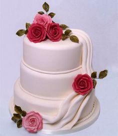 A typical three-tiered round wedding cake with red and pink roses.