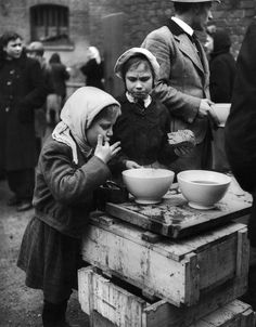 Russian children eat molasses bread at a refugee camp, April, 1945