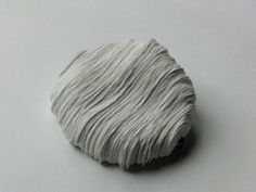 Lisa Catterson - White Contour Brooch - Brooch, oxidised silver and white handmade paper, hand cut from templates made using 3D drawing programme. Inspired by changing contours of fleshy section within mushroom. (Glasgow School of Art Silversmithing and Jewellery BA (Hons)