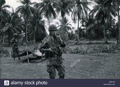 GI smoking cigarette, holding M16 on patrol. 101st ABN in the Ashau Valley during the Vietnam War.