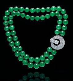 An exclusive double-strand jadeite bead and diamond necklace. Estimate HK$28,000,000 – HK$38,000,000 ($3,629,808 - $4,926,168). Photo Christie's Image Ltd 2015 Composed of sixty jadeite beads, measuring approximately 11.7 to 14.5 mm, to a detachable circular clasp, set with circular, single and square-shaped diamonds, centering upon a rectangular-cut diamond, mounted in platinum, necklace 40.5 cm, brooch 3.4 cm. Clasp signed Cartier, no. 3615779