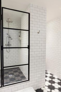 Clad in white subway all tiles accented with dark grout, this contemporary black and white bathroom features black and white floor tiles leading to a marble step positioned in front of a glass and steel enclosed walk in shower fitted with black hex floor tiles framed by a white subway tile surround finished with corner nook shelves and a vintage nickel exposed plumbing shower kit.