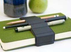 This is nifty: A leather strap fitted with small loops for carrying pens, pencils, and other handy tools wrapped around a journal.