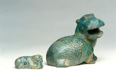 Two Faience Hippopotami Middle Kingdom, Dynasty 12, 1800 BC. Among the numerous faience figurines of the Middle kingdom varying in color from dark to light green and blue, the small hippopotamus figurines have a special position. The animal was represented very realistically and the plants, such as water lilies, papyrus and lotus plants, representing the environment in which they lived, were painted on their bodies.