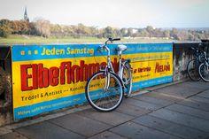 Werbeplakat vom Elbeflohmarkt auf einer Brücke mit einem Fahrrad davor