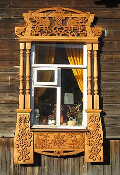 Elaborately carved window frame on Russian wooden house.  Don't know the purpose of the tiny window-within-a-window, but it looks like it might be the only piece that opens.
