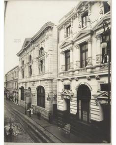 Calle Prat de Valparaíso y el ingreso al Ascensor Concepción, entre los edificios del antiguo Banco Alemán Trasatlántico (izquierda) y el Banco de Tarapacá y Londres (derecha), ambos construidos por el arquitecto Esteban Harrington.   --  Fecha de la Fotog. c.1910   ---   MHN