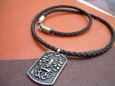 A beautiful stainless steal Fleur De Lis dog tag pendant ( approx. 1 x 1 3/4 inch) hangs from this premium quality braided leather cord