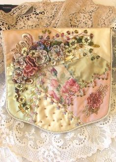 A beautiful textured needlecase worked in crazy patchwork. The needlecase is patched with Dupion silks and Jacquard fabric, all encrusted with hand dyed lace, hand dyed Hanah silk ribbons and various silk threads.