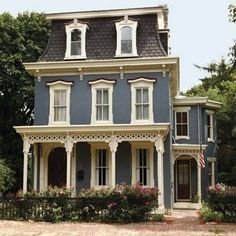 love this color scheme (minus the burgundy above the window frames)...the gray/blue main with creamy white  trim and black accents, charcoal roof...and either a red or natural wood door.