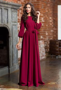A woman is wearing an elegant and romantic red magenta maxi dress
