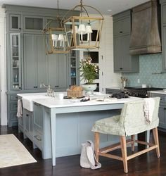 Gorgeous kitchen features green cabinets painted Sherwin Williams Retreat paired with white marble countertops and Tabarka Studio Artisan Terracotta Fan Tile in Robin's Egg Blue.