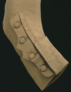 Thick wool fabric lends a sculptural quality to the 'mariner's cuff' on this strictly utilitarian garment. Such a style of cuff was first seen on the coats worn by naval officers in the 1740s (navy uniform was not made official until 1748) and became a popular feature of both men's fashionable coats and ladies' riding jackets. A vertical opening with a scalloped flap runs parallel to the length of the sleeve and intersects the cuff.