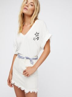 Shear Me Up Buttercup Tee | Comfy cotton tee featuring a modern asymmetric hemline with cute embroidered star graphics.    * Unfinished edges for a lived-in look * V-neckline * Side vent * Semi-sheer fabrication