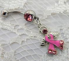 Belly button piercing ring with adorable pink ribbon angel with wings with lovely Swarovski pink crystals on ribbon. The belly ring is 3/4 in. (1.90cm) in length and is attached to a 14ga surgical ste