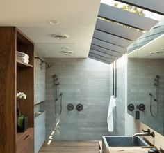 In this modern bathroom, a large skylight keeps the space feeling bright and open, while a glass shower screen separates the two person shower from the rest of the bathroom. The one level wall in shower is simple to enter and exit Two Person Shower, Knock Down Wall, Architecture Design, 1960s House, Stone Accent Walls, Modern Master Bathroom, Small Bathroom, Bathroom Wall Decor, Bathroom Ideas