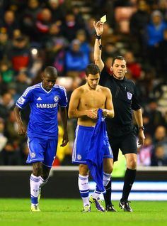Eden Hazard Photos - Referee Phil Dowd shows the yellow card to Eden Hazard of Chelsea after his second goal celebration during the Barclays Premier League match between Sunderland and Chelsea at Stadium of Light on December 4, 2013 in Sunderland, England. - Sunderland v Chelsea