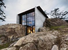 The Pierre Home, San Juan Islands, Washington Approach this house from the rear and you won't see anything but a mossy outcropping. A closer look, though, reveals a 2,200-square-foot glass-fronted home that looks over the Pacific Ocean. Designed by Tom Kundig of Olson Kundig Architects, the Washington state home was built into rock. Most of the living space is submerged beneath the earth. A wide-open terrace with sweeping views of water life including sea lions and killer whales.