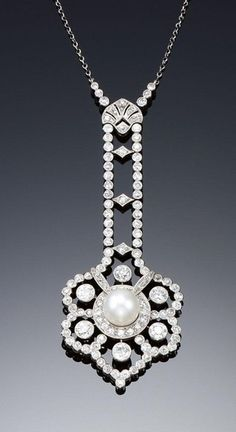 CULTURED PEARL AND DIAMOND NECKLACE, CIRCA 1910. Centring on an open work flower head pendant millegrain set with circular- and single-cut diamonds, encircling a cultured pearl centre