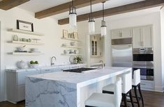 Transitional kitchen features three modern frosted glass column pendants illuminating a gray and white marble waterfall island fitted with a gas cooktop lined with white leather barstools.