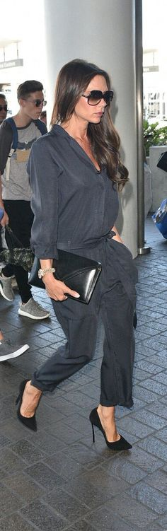 Victoria Beckham in a black jumpsuit cinched at the waist, retro shades, a black envelope clutch and suede stilettos