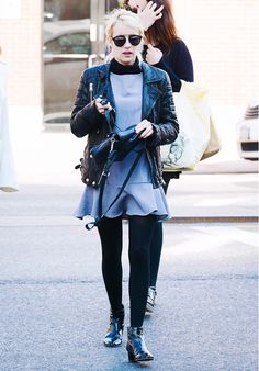 Emma Roberts wears a gray dress, leather jacket, leggings, patent leather boots, and Dior sunglasses